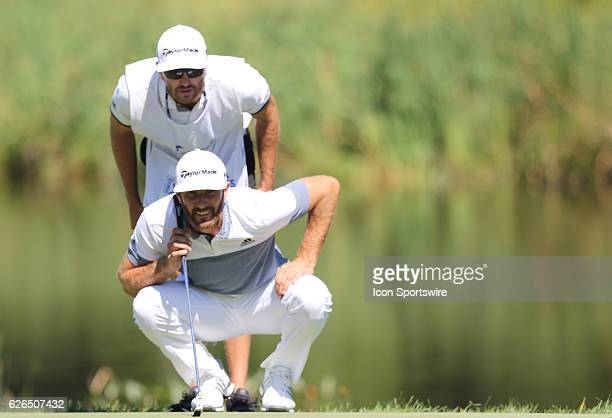 Dustin Johnson and his caddie analyze the green during the opening round of the Deutsche Bank Championship at the TPC Boston in Norton Ma