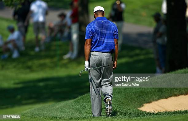 Tiger Woods walks with his head down after hitting a ball out of a bunker in round one of the BMW Championship at Cog Hill Golf and Country Club in...