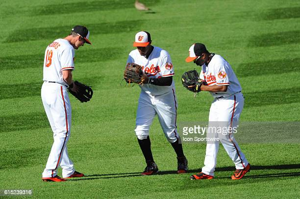 Baltimore Orioles center fielder Drew Stubbs center fielder Adam Jones and right fielder Michael Bourn bow in the outfield following the game against...