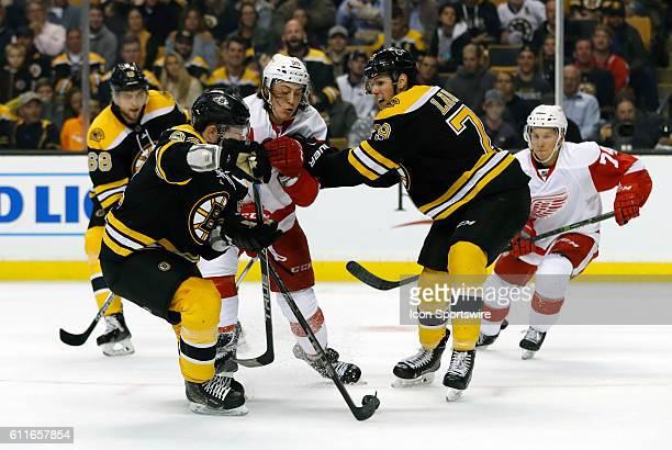 Boston Bruins forward Jesse Gabrielle and Boston Bruins left defenseman Jeremy Lauzon sandwich Detroit Red Wings forward Tyler Bertuzzi The Detroit...