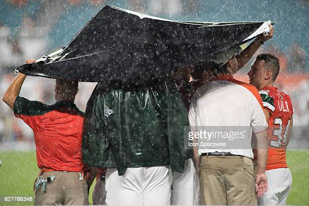 Miami Hurricane teammates and coaches trying to find some shelter from the rain during the NCAA football game between the Florida Atlantic Owls and...