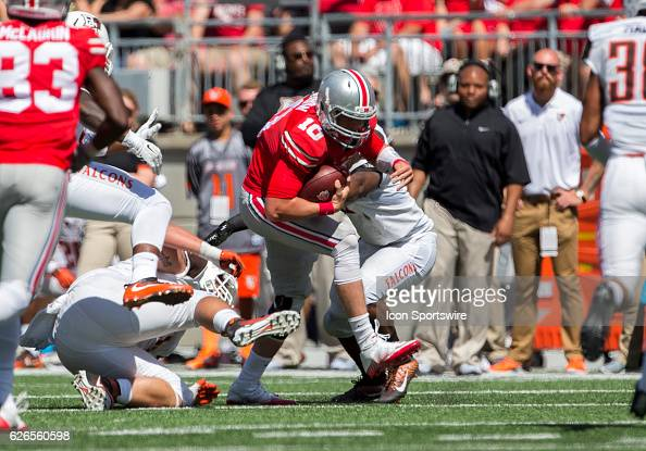 Ohio State Buckeyes quarterback Joe Burrow slips through the defensive players for a first down during the game between the Bowling Green Falcons and...