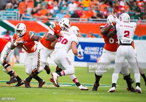 University of Miami Hurricanes Running Back Mark Walton runs with ball as University of Miami Hurricanes Offensive Lineman Trevor Darling blocks...