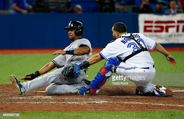 TORONTO ON September 22 2015 New York Yankees right fielder Chris Young gets tagged out at home by Toronto Blue Jays catcher Dioner Navarro during...
