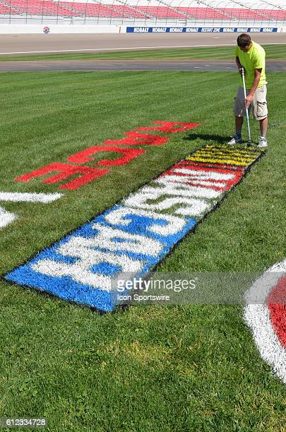 Painter completes the final touches on the infield NASCAR logo during the NASCAR Camping World Truck Series DC Solar 350 at Las Vegas Motor Speedway...