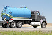 Side view of a pump truck hauling sewage removed from a residential septic tank.
