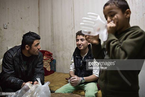 Serbest and Serdesht chat while Ezidiar blows a plastic glove into a balloon The family of Yezidis displaced from Sinjar live next to an oil refinery...