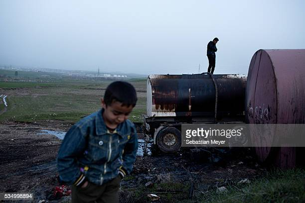 Serbest talks on the phone while he waits for a tanker to fill up with fuel oil Ezidiar plays in the foreground The family of Yezidis displaced from...
