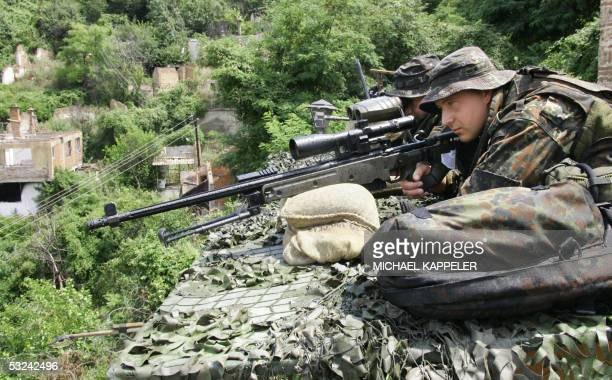 German KFOR soldiers look through a sniper rifle securing the area during the visit of German opposition leader head of the Christian Democratic...