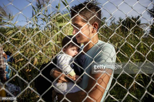 Serbia Horgos Refugee holding baby at wired fence short after closing Hungarian border Hungary has been a major transit country for migrants many of...