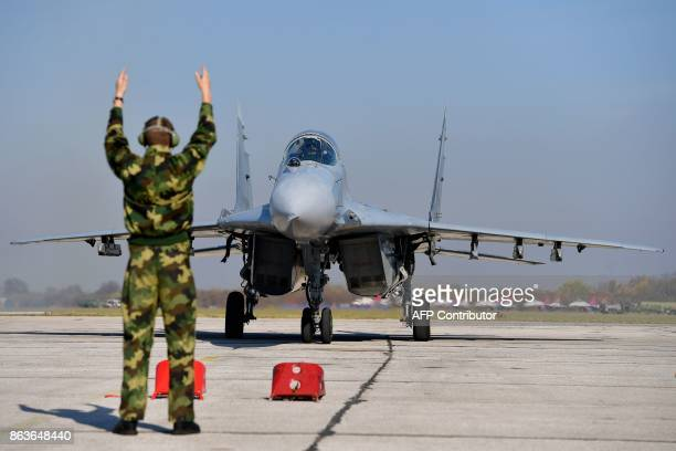 A Serbian Army MiG29 jet fighter rolls over the tarmac during a ceremony at Batajnica military airport near Belgrade on October 20 2017 Russia...