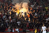 Serbian fans burn a NATO flag on October 14 2014 during a Euro 2016 group I qualifying football match between Serbia and Albania in Belgrade The...