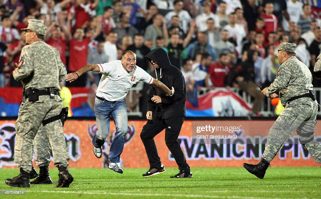 Serbian fans invade the pitch after the UEFA Euro 2016 group I qualifying football match between Serbia and Albania in Belgrade was stopped after a...