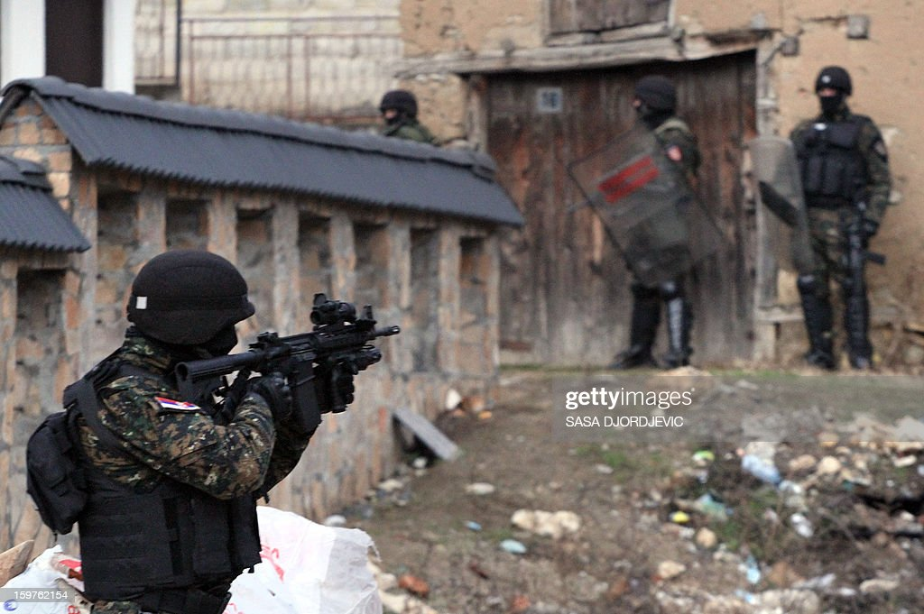 A Serbian gendarme points his rifle as part of an operation to secure the area during removing of the monument of the Liberation Army of Presevo, Medvedja and Bujanovac (UCPMB) in the town of Presevo on January 20, 2013. Serbian authorties removed early in the morning the monument eracted in the ethnic Albanian stronghold town of Presevo and dedicated to the fighters in the 2001 conflict against Serbian security forces. The monument, dedicated to the fallen members of the Liberation Army for Presevo, Medvedja and Bujanovac, whose goal was to unite the ethnic Albanian majority area in the Presevo Valley with neighbouring Kosovo, was erected in November in front of the ethnic-Albanian-run municipality building in Presevo.