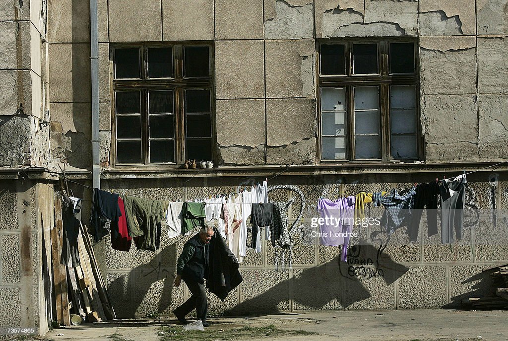 A Serbian grabs laundry from outside an abandoned school he's lived in for eight years after fleeing his village in Albanian-dominated Kosovo March 14, 2007 in Mitrovica, Kosovo. Before 1999 Mitrovica was a town where Serbs and ethnic Albanians lived side-by-side. It is now is Kosovo's most glaring symbol of separation, as the two populations quickly separated themselves after the fall of the Serbian government in Kosovo and occupied opposite banks of the Ibar river. Serbs fleeing from ethnic Albanian reprisal attacks fled to Serbian northern Mitrovica in 1999, settling down in an abandoned school, where they remain.