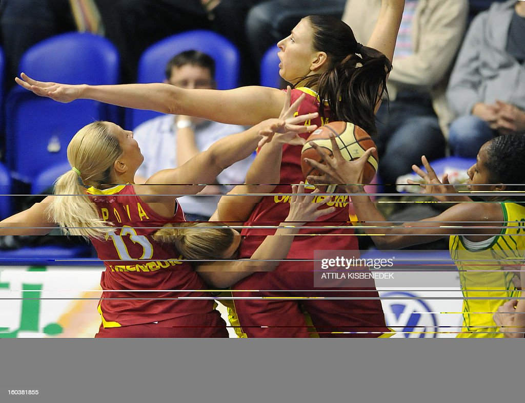 Serbian Jelena Milovanovic of Hungarian UE Sopron fights for the ball between Liudmila Sapova (L) and Tamane Zane (2nd R) of Russian Nadezhda Orenburg on January 30, 2013 during their basketball EuroLeague match in Sopron, Hungary.