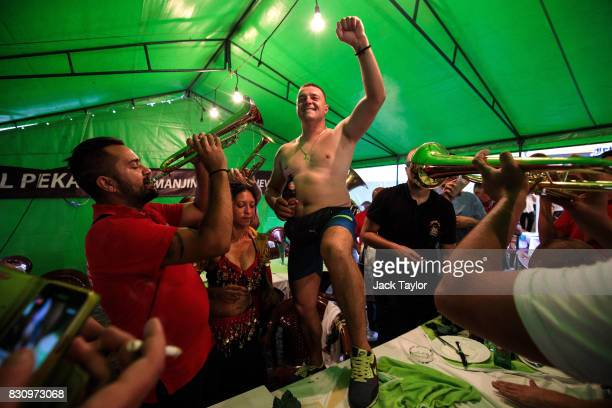 Serbian man raises his fist into the air as a brass band plays in a restaurant during the Guca Trumpet Festival on August 11 2017 in Guca Serbia...