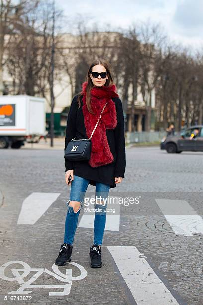 Serbian model Mina Cvetkovic wears a black sunglasses big chunky red fur stole over a black sweater with a black Louis Vuitton purse jeans ripped at...