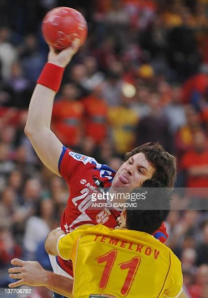 Serbian Momir Rnic throws the ball past Macedonian Vladimir Temelkov during the Men's EHF Euro 2012 Handball Championship match between Serbia and...