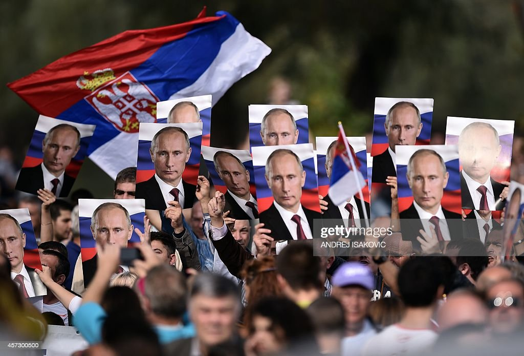 Serbian nationalists hold posters showing Russian President Vladimir Putin ahead of a military parade in Belgrade on October 16 2014 Vladimir Putin...
