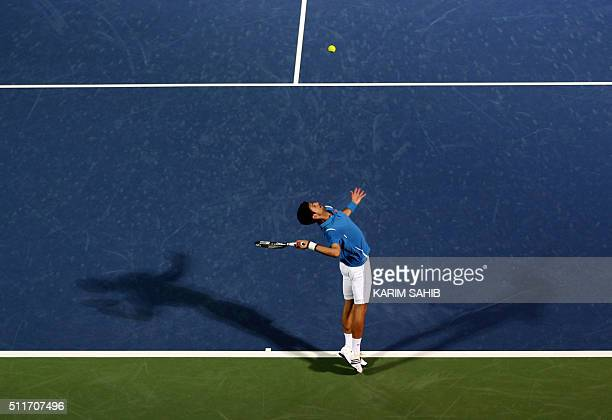 TOPSHOT Serbian Novak Djokovic serves the ball to Spanish Tommy Robredo during their ATP tennis match on the first round of the Dubai Duty Free...