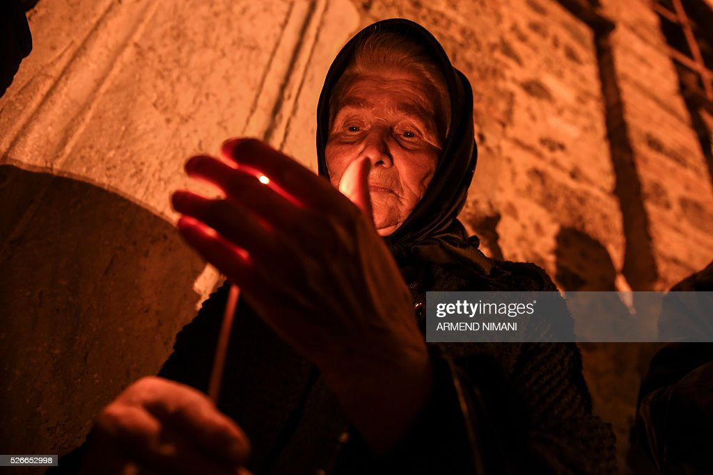 A Serbian Orthodox believer holds a candle during Orthodox Easter religious services in the Medieval Monastery in the town of Gracanica on April 30, 2016. Orthodox Christian believers mark the Holy Week of Easter in celebration of the crucifixion and resurrection of Jesus Christ. / AFP / ARMEND