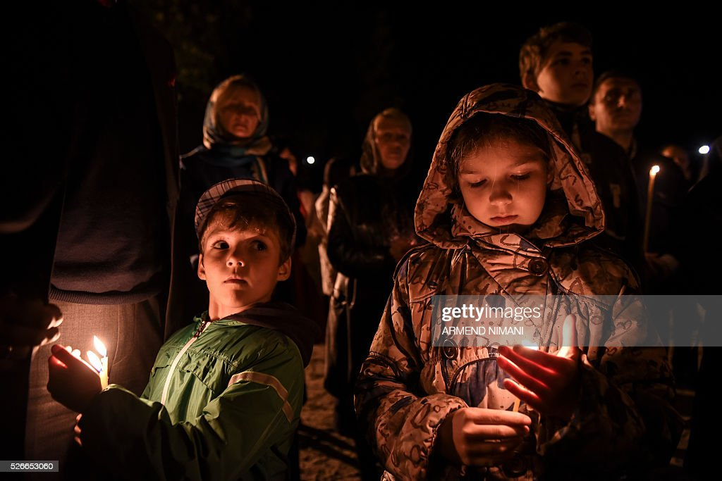 Serbian Orthodox believers hold candles during Orthodox Easter religious services in the Medieval Monastery in the town of Gracanica on April 30, 2016. Orthodox Christian believers mark the Holy Week of Easter in celebration of the crucifixion and resurrection of Jesus Christ. / AFP / ARMEND