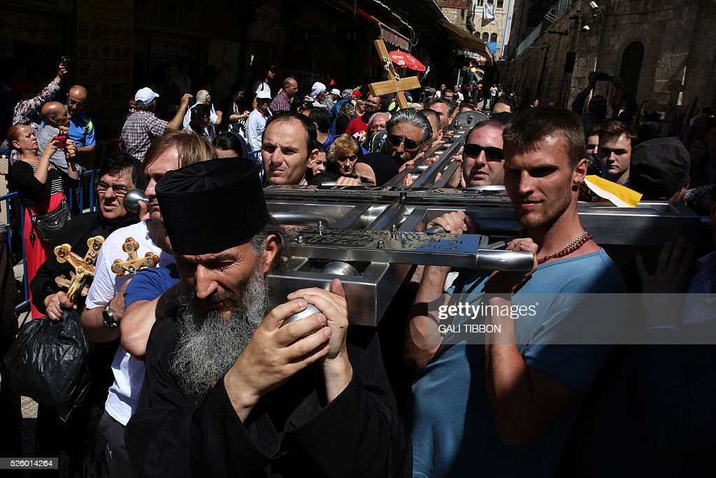 Serbian Orthodox Christian pilgrims carry a large metal cross from Serbia along the Via Dolorosa (Way of Suffering), during the Good Friday procession in Jerusalem's old city on April 29, 2016. Thousands of pilgrims took part in processions along the route where, according to tradition, Jesus carried the cross during his last days. / AFP / GALI