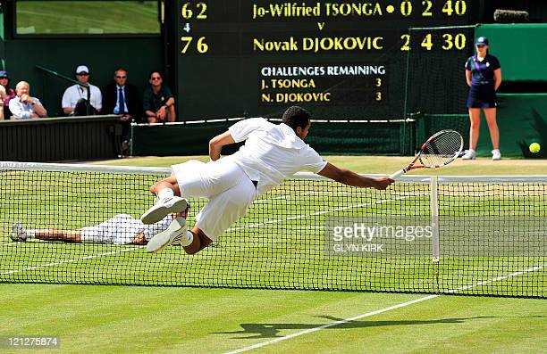 Serbian player Novak Djokovic lies on the ground as French player JoWilfried Tsonga returns a shot during the men's single semi final at the...
