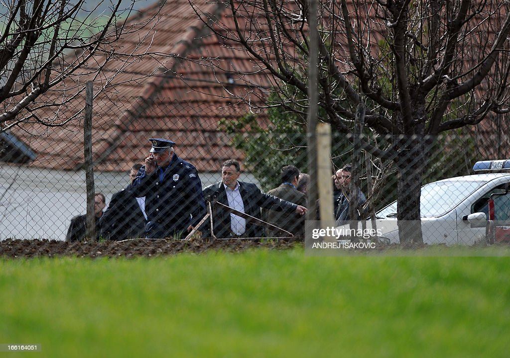 Serbian police officer inspect a back yard of a house in the village of Velika Ivanca, 40 kilometres south of capital Belgrade, on April 9, 2013, where a man shot dead 13 relatives and neighbours, including a two-year-old child, in the country's worst killing spree in two decades..