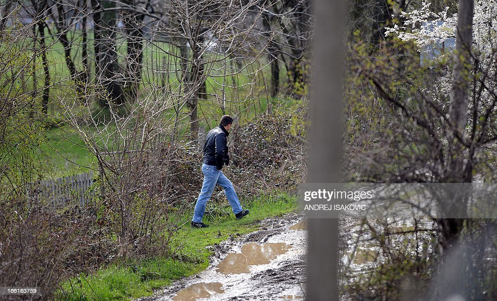 A Serbian police officer inspects a road in the village of Velika Ivanca, 40 kilometres south of capital Belgrade, on April 9, 2013, where a man shot dead 13 relatives and neighbours, including a two-year-old child, in the country's worst killing spree in two decades..