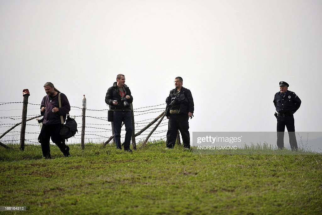 A Serbian police officer orders photographers to leave the vicinity of the site where a man shot dead 13 relatives and neighbours, including a two-year-old child in the village of Velika Ivanca, 40 kilometres south of capital Belgrade, on April 9, 2013.