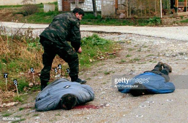 A Serbian police officer secures evidence at the spot where two of his colleagues were shot dead in the center of Malisevo a former stronghold of the...