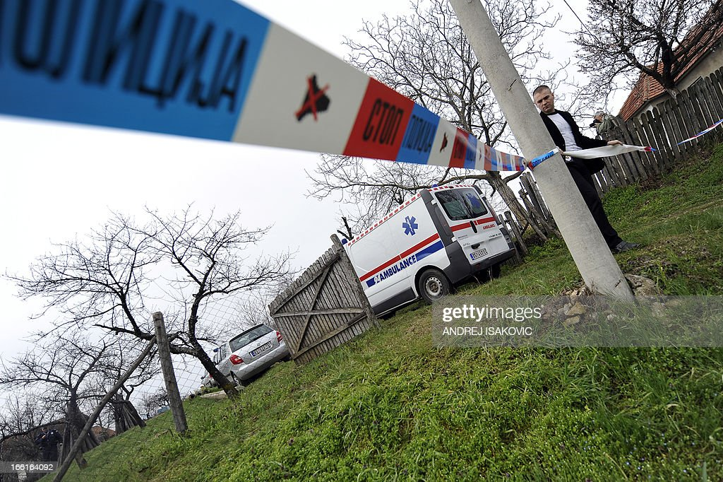 A Serbian police officer sets a security perimeter at the entrance of a yard in the village of Velika Ivanca, 40 kilometres south of capital Belgrade, on April 9, 2013, where a man shot dead 13 relatives and neighbours, including a two-year-old child, in the country's worst killing spree in two decades..