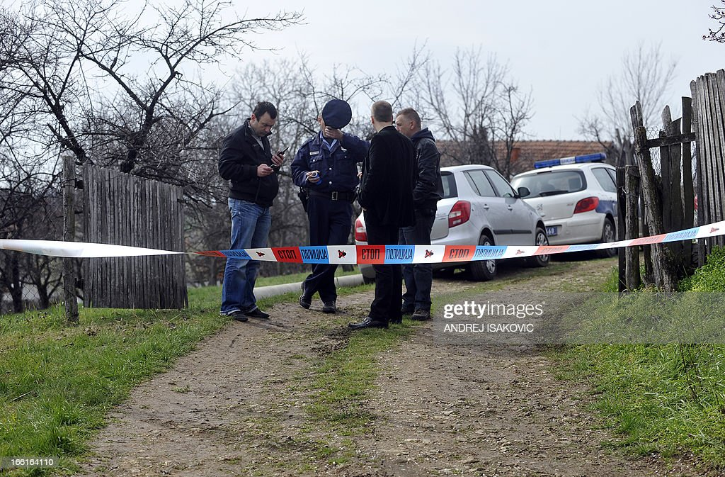 Serbian police officers guard entrance to a yard in the village of Velika Ivanca, 40 kilometres south of capital Belgrade, on April 9, 2013, where a man shot dead 13 relatives and neighbours, including a two-year-old child, in the country's worst killing spree in two decades.