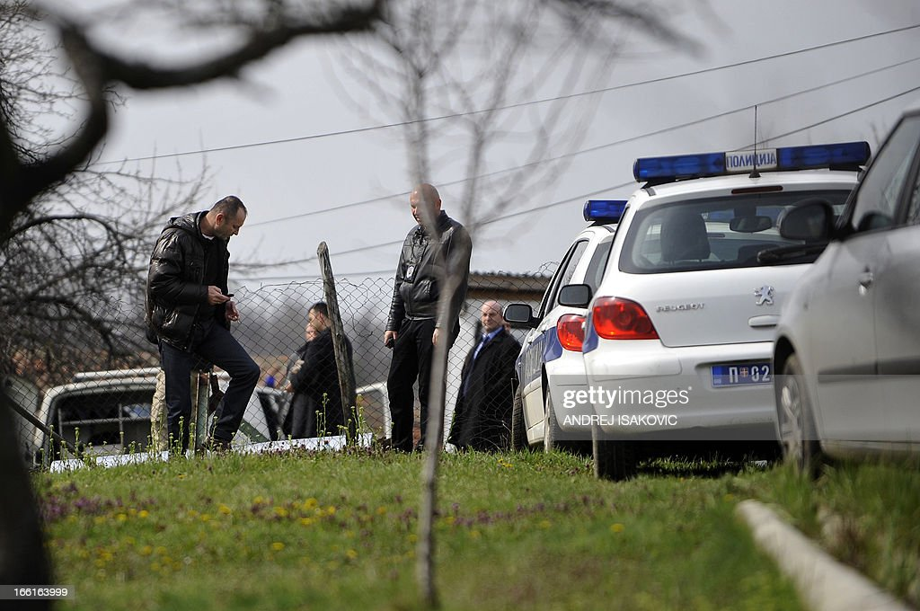 Serbian police officers inspect a back yard of a house in the village of Velika Ivanca, 40 kilometres south of capital Belgrade, on April 9, 2013, where a man shot dead 13 relatives and neighbours, including a two-year-old child, in the country's worst killing spree in two decades..
