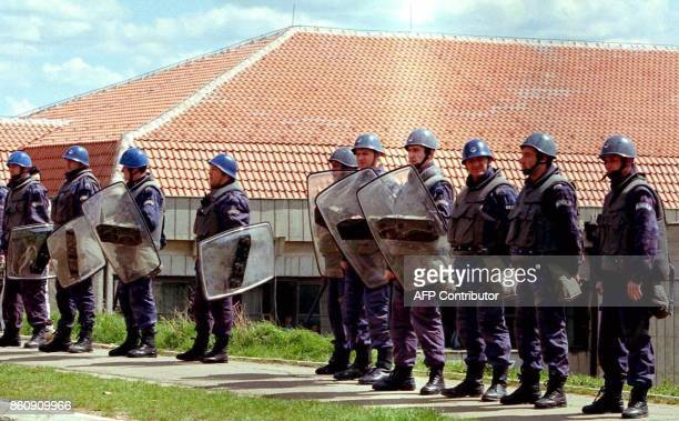 Serbian policemen stand in front of the Technical University of Pristina and prevent ethnic Albanian students from entering the building following an...