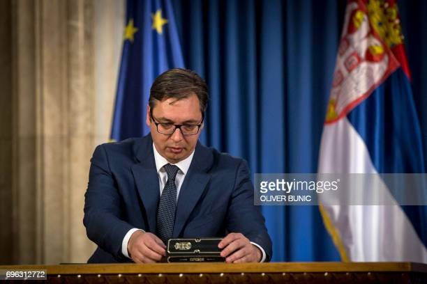 Serbian President Aleksandar Vucic prepares to sign the decree appointing serbia's new prime minister during a press conference in Belgrade on June...