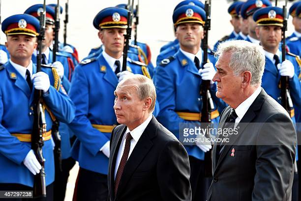 Serbian President Tomislav Nikolic and his Russian counterpart Vladimir Putin review an honor guard on October 16 2014 in Belgrade Putin was expected...