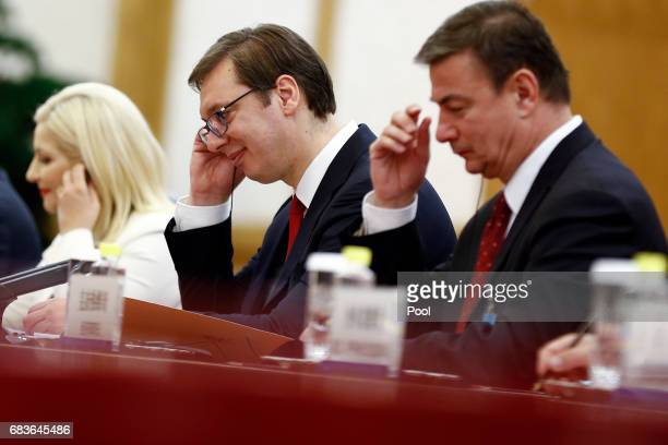 Serbian Prime Minister Aleksandar Vucic adjusts earphones as he listens to Chinese President Xi Jinping as they meet at the Great Hall of the People...