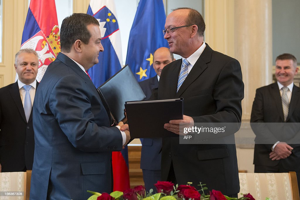 Serbian Prime Minister and Minster of Interior Ivica Dacic (L) and Slovenian Minister of Interior Vinko Gorenak shake hands after signing an agreement on police cooperation between Serbia and Slovenia during a meeting in Ljubljana on November 14, 2012. AFP PHOTO / JURE MAKOVEC