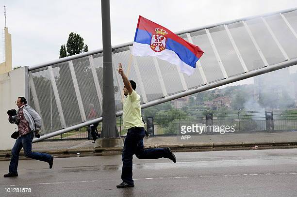 A Serbian protester runs and waves a Serbian flag during a protest in the divided town of Mitrovica on May 30 2010NATO peacekeepers and Kosovo riot...