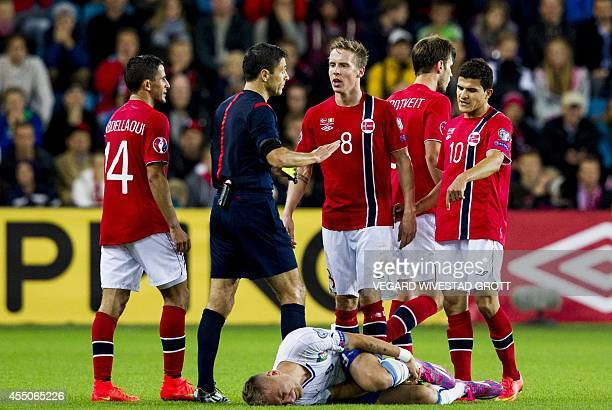 Serbian referee Milorad Mazic instructs Norway's players as Italy's striker Ciro Immobile lies injured on the pitch during the UEFA Euro 2016 Group H...