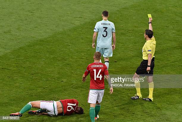 Serbian referee Milorad Mazic presents Belgium's defender Thomas Vermaelen with a yellow card following a tackle on Hungary's midfielder Adam Pinter...