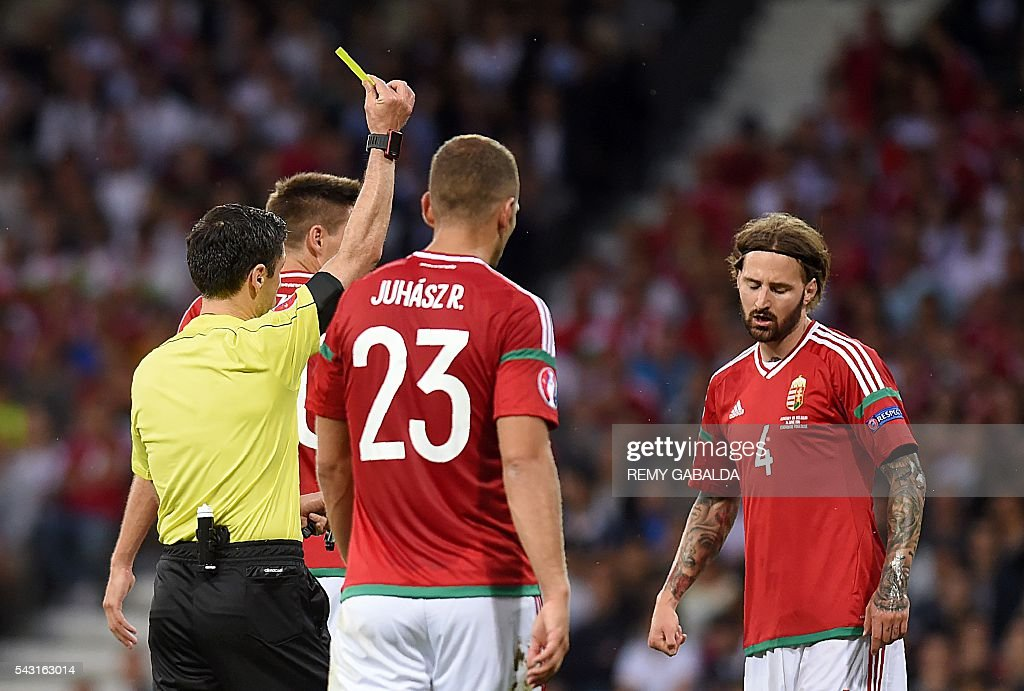 Serbian referee Milorad Mazic (L) presents Hungary's defender Tamas Kadar (R) with a yellow card during the Euro 2016 round of 16 football match between Hungary and Belgium at the Stadium Municipal in Toulouse on June 26, 2016. / AFP / Rémy GABALDA