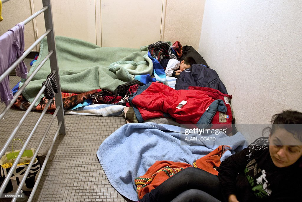 A Serbian refugees family sleeps in a building foyer on December 18, 2012, in Tours, central France. AFP PHOTO/ALAIN JOCARD