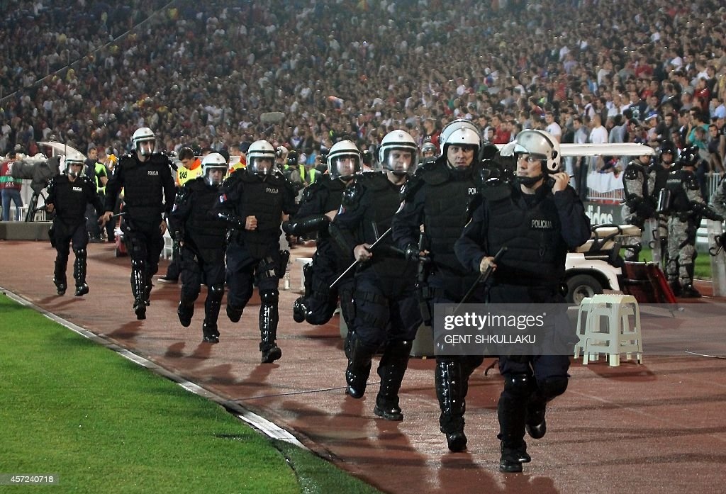 Serbian riot policemen arrive to secure the pitch after a flag with Albanian national symbols was flown by a remotely operated drone during the UEFA...