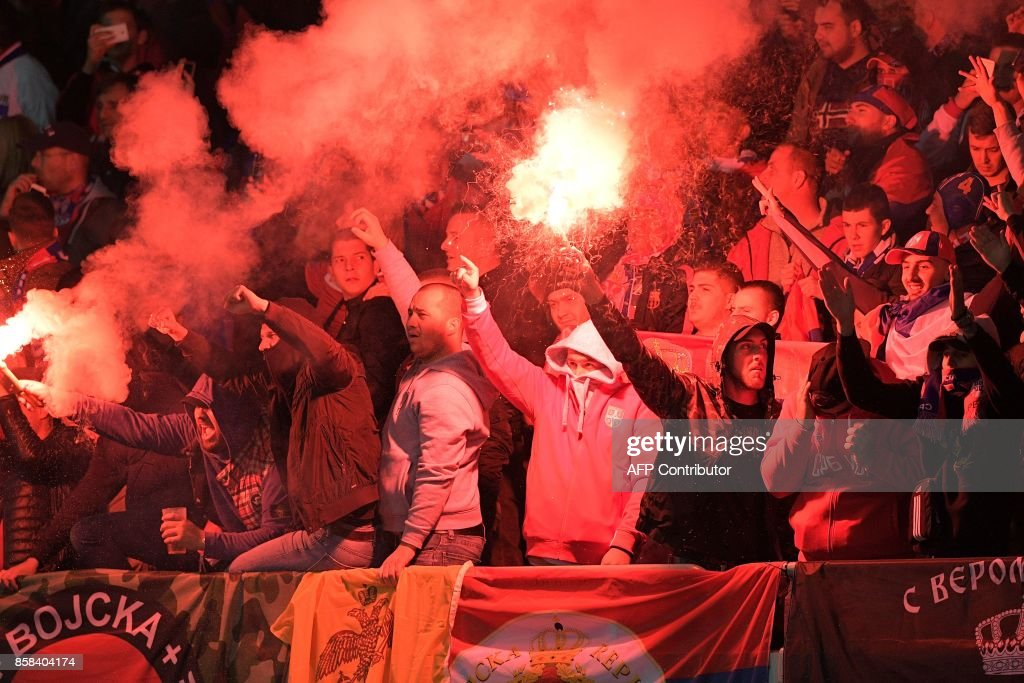 Serbian supporters light flares as they celebrate after their team scored during the FIFA World Cup 2018 qualification football match between Austria and Serbia at the Ernst Happel stadium in Vienna on October 6, 2017. /