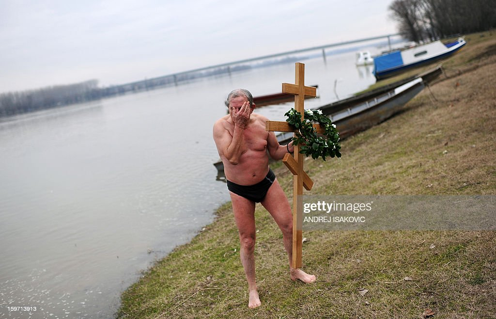 A Serbian swimmer holds the cross after it was retrieved from the cold waters of the Sava river in Sabac, 80 kilometres west of capital Belgrade on Epiphany day, on January 19, 2013. According to a popular belief, the first man to pick up the cross, thrown on Epiphany day into the water by an Eastern Orthodox priest, will be healthy throughout the New Year. AFP PHOTO / ANDREJ ISAKOVIC