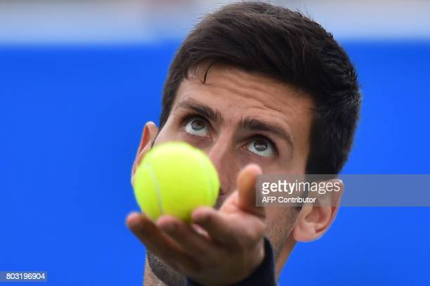 TOPSHOT Serbian tennis player and world number four Novak Djokovic serves to Donald Young of the US during their men's singles quarter final tennis...